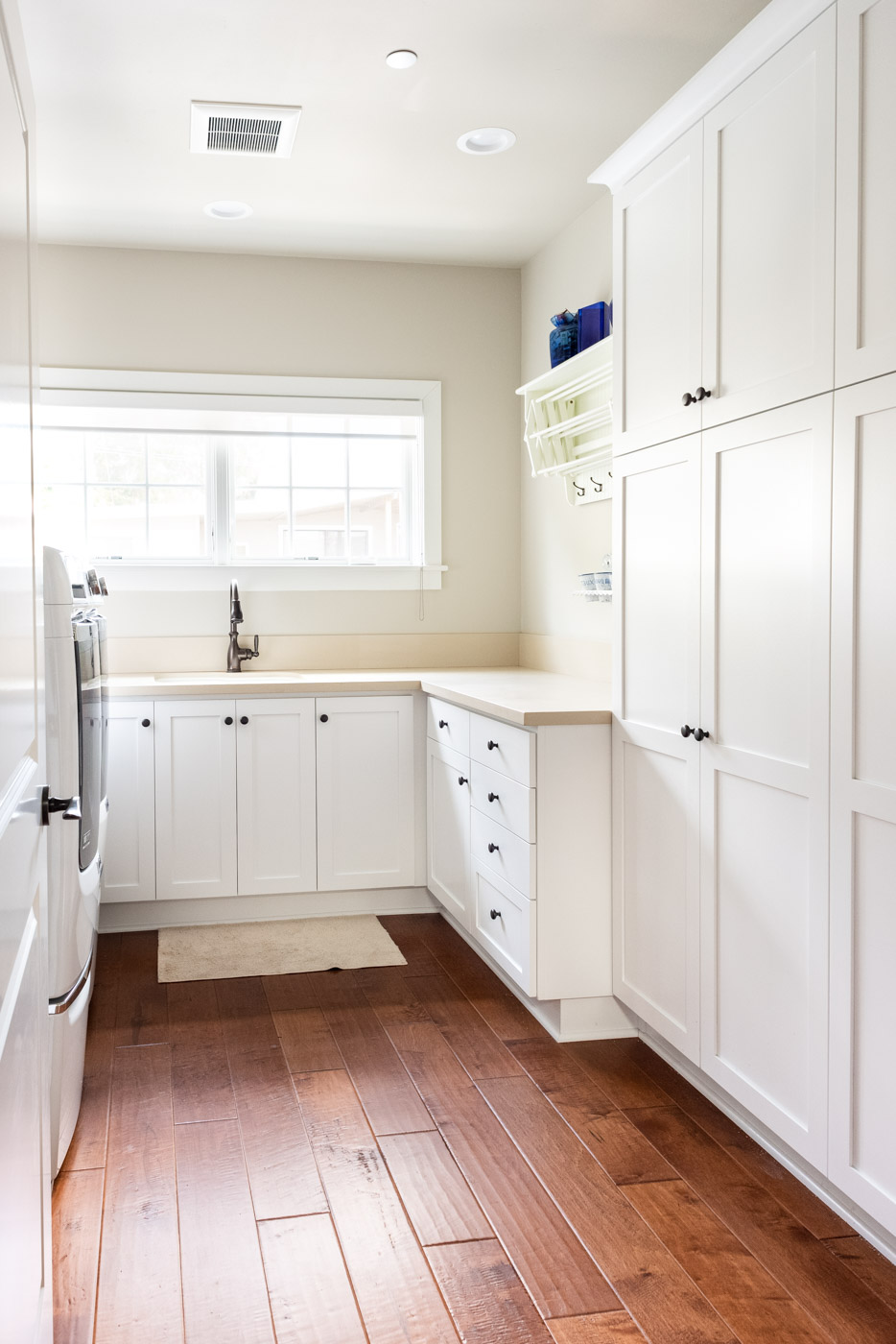 Coastal Craftsman home with custom white painted laundry room cabinets