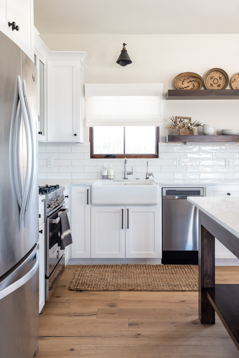 Vineyard Guest House kitchen with custom white painted shaker cabinets farmhouse sink and open shelving