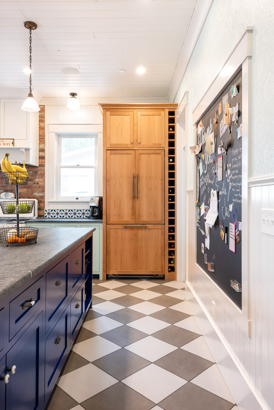 Eclectic Country Craftsman kitchen with custom blue painted cabinets and stained wood refrigerator door panels