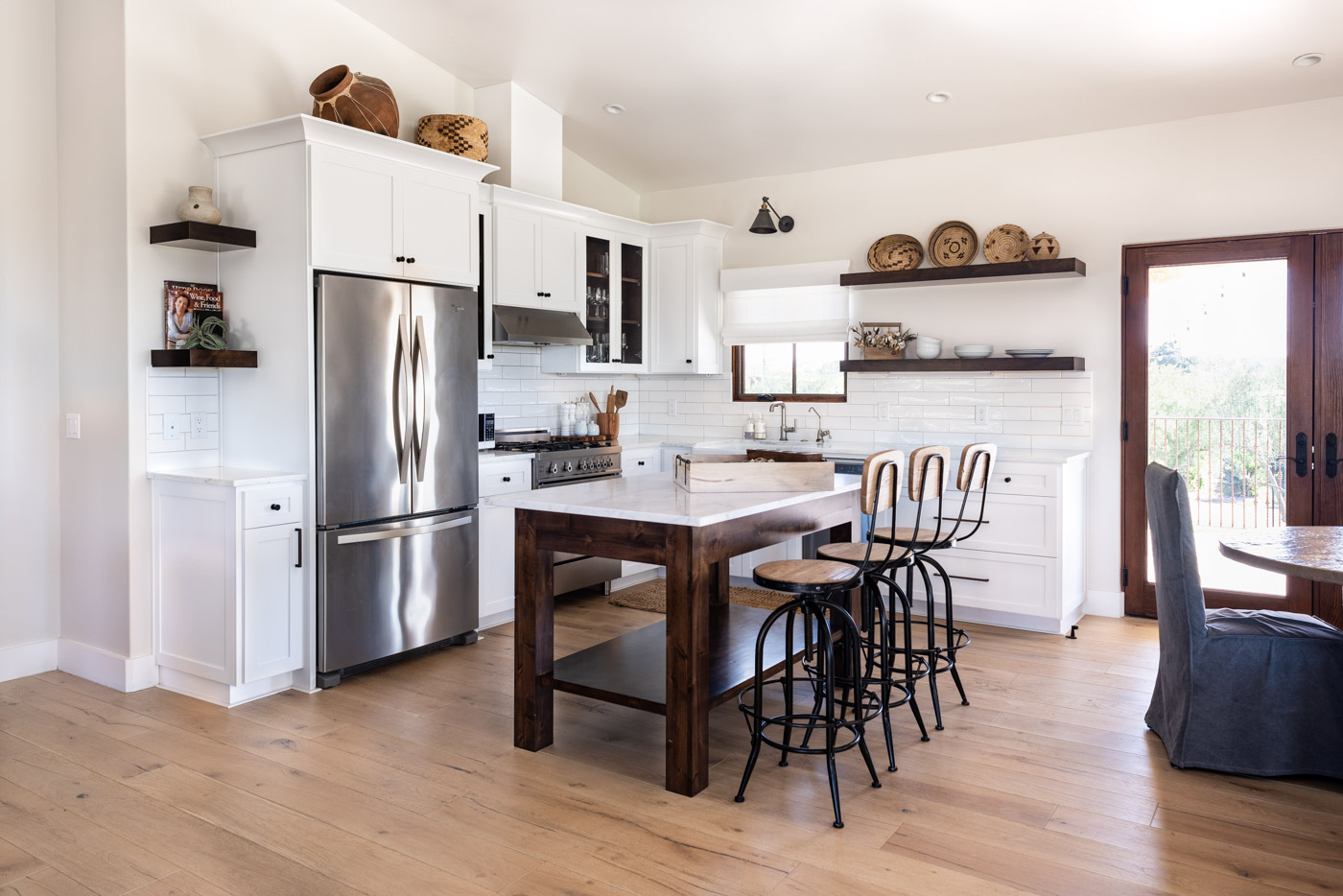 An L-shaped kitchen layout with custom white painted cabinets and free-standing wood island