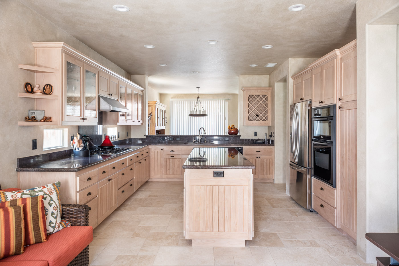 A u-shaped kitchen layout with small island and custom white-washed wood cabinets