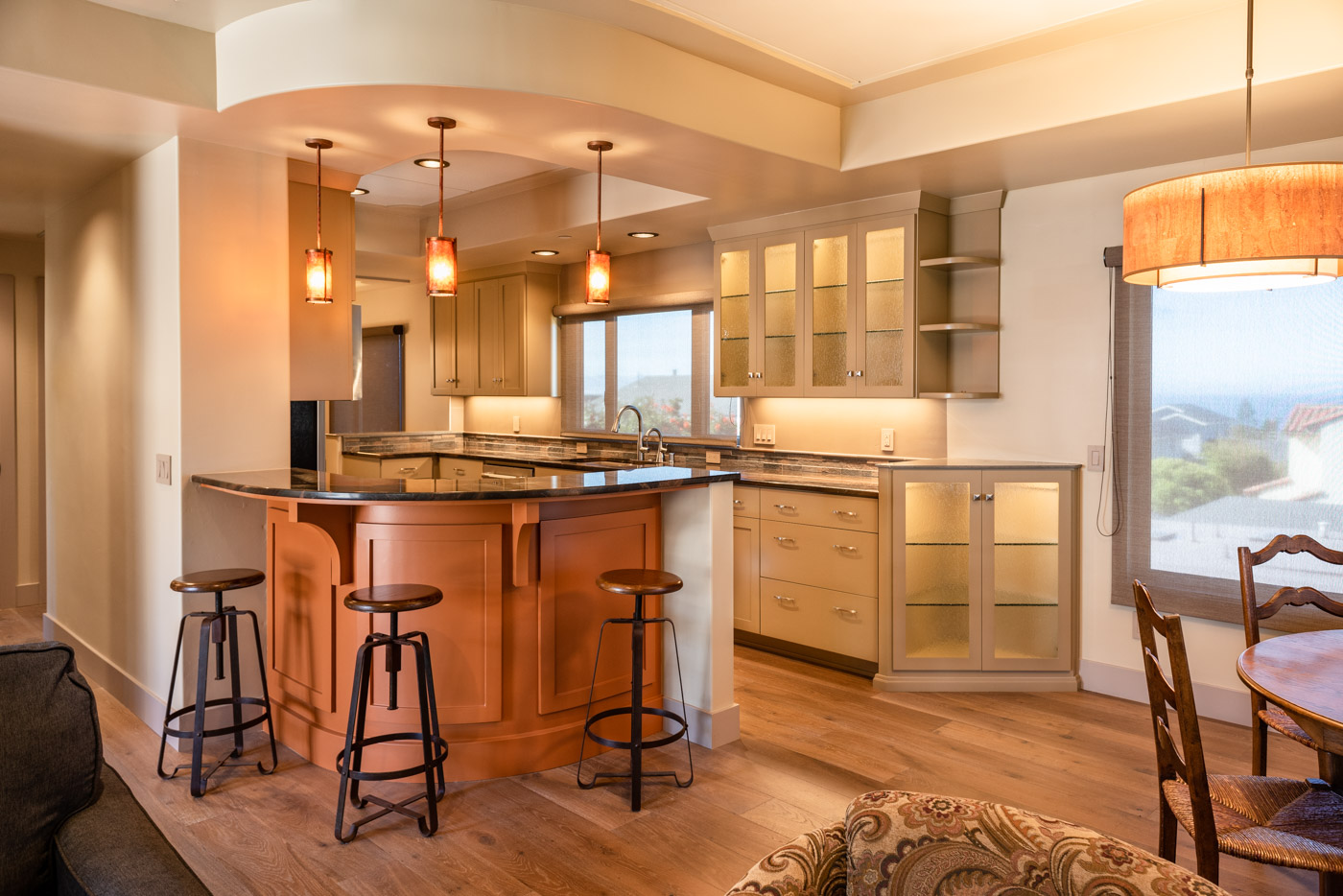 A G-shaped kitchen layout with custom orange and beige painted cabinets