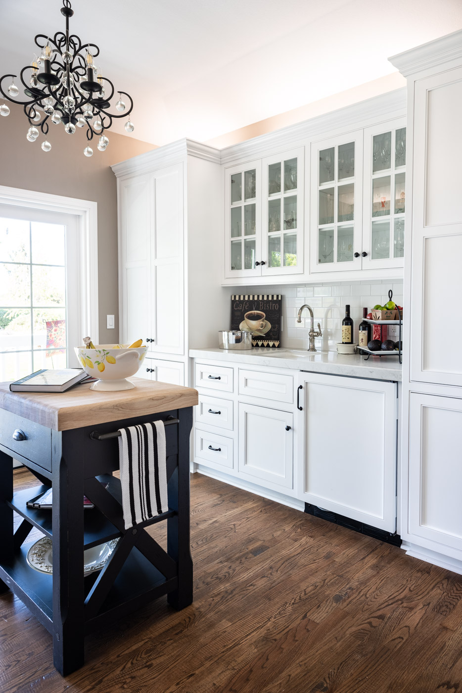 A tea room single-wall kitchen layout used as a home bar with custom white painted cabinets