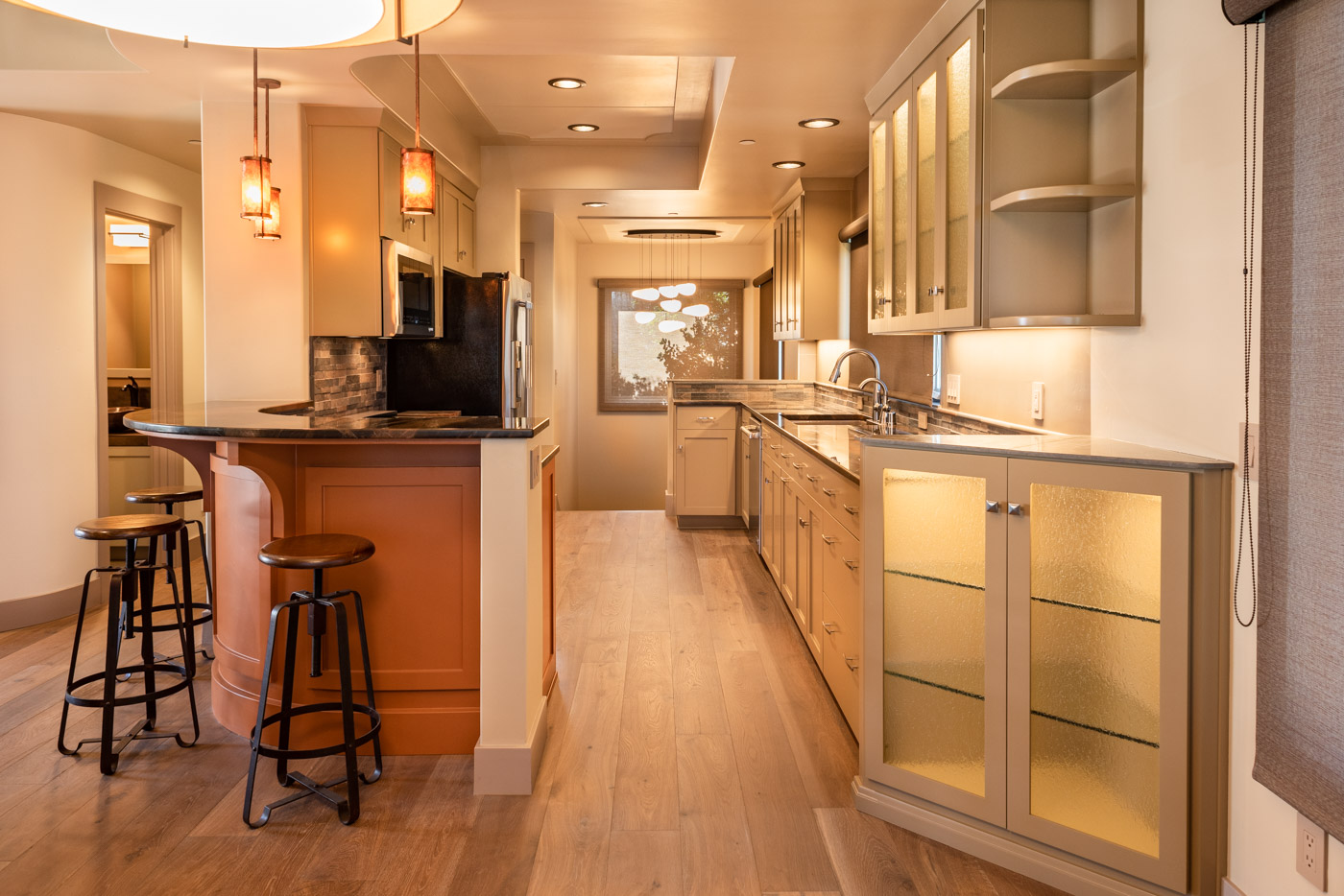 A Galley kitchen layout with custom orange and beige painted cabinets and bar seating