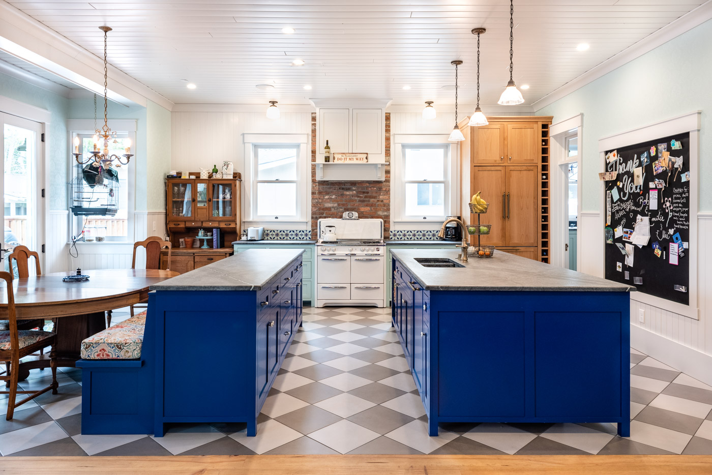 A galley kitchen layout with an eclectic style and two kitchen islands with custom painted blue cabinets