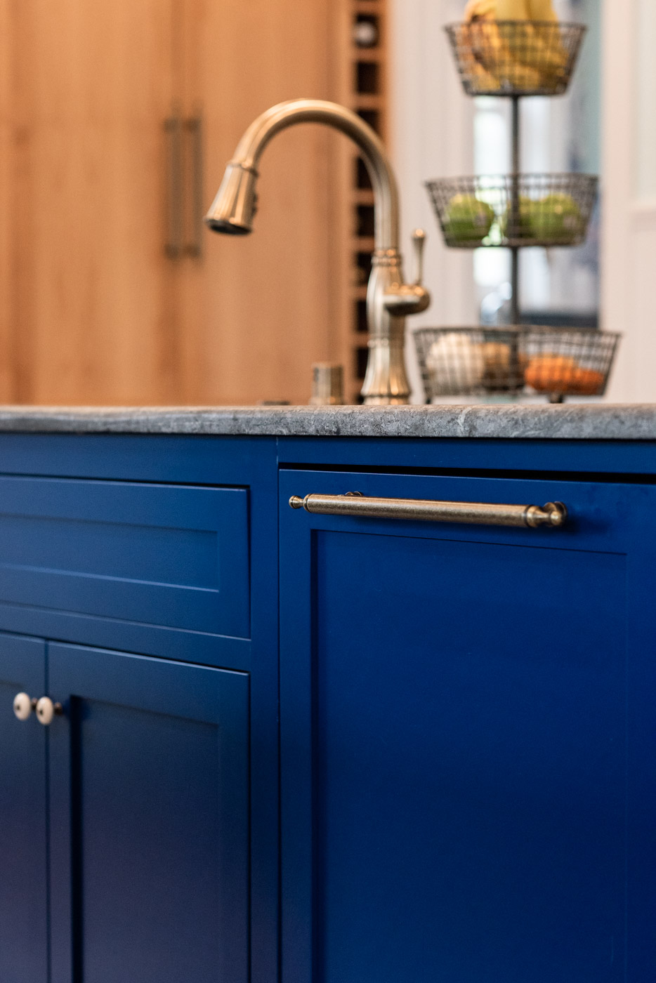 A mix of knobs and bar pull kitchen cabinet hardware in a brass finish against blue custom painted cabinets