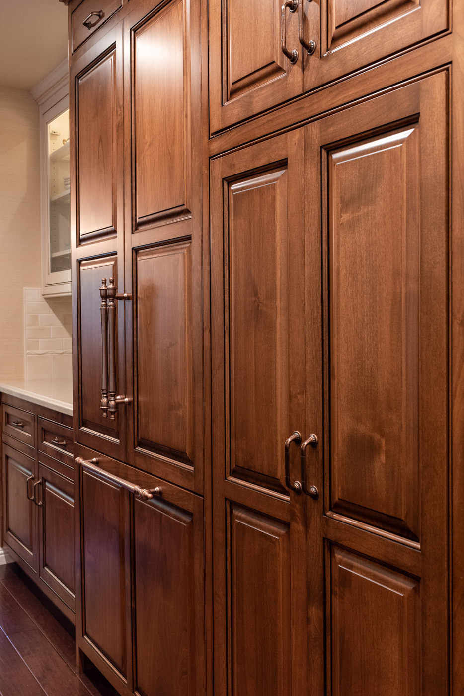 English Country custom kitchen cabinets with wood refrigerator door panels