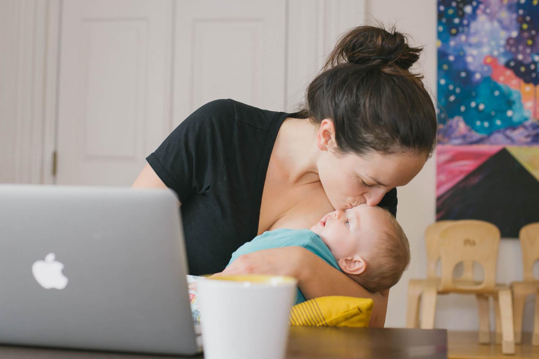 Mama kissing baby in work space.jpg