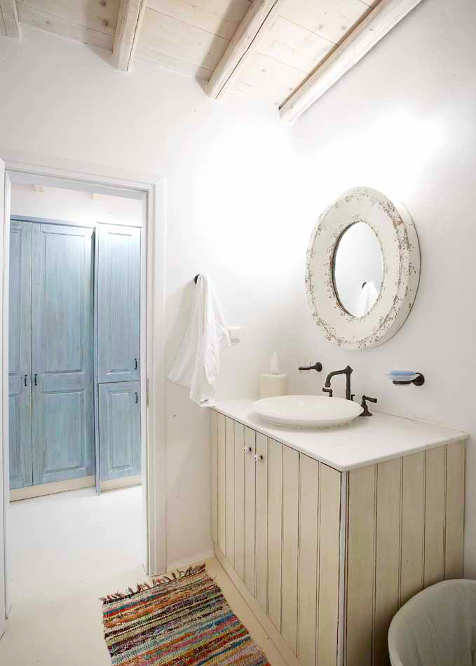 Greek island style bathroom with blue and white cabinetry.