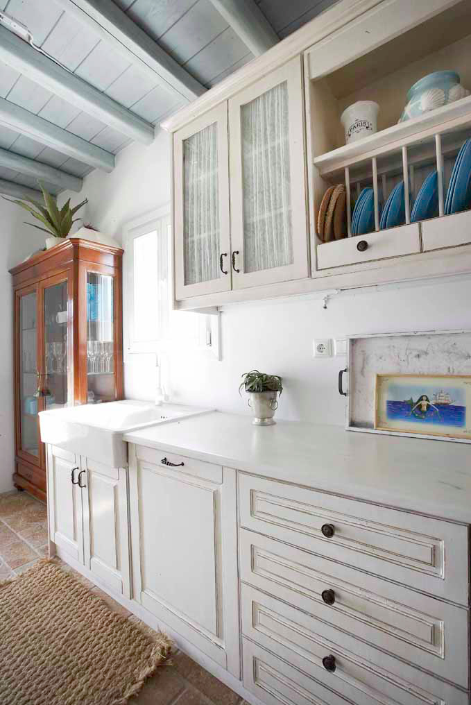 Greek island style kitchen with white cupboards and blue details.