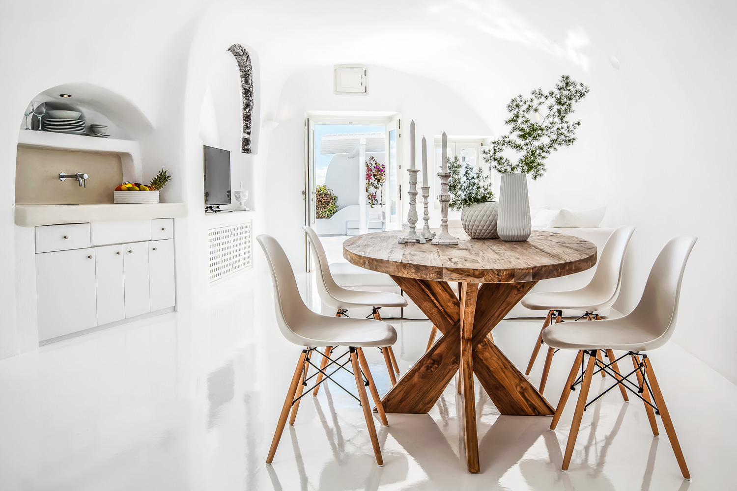 Greek island dining room with rustic wooden table and modern chairs.