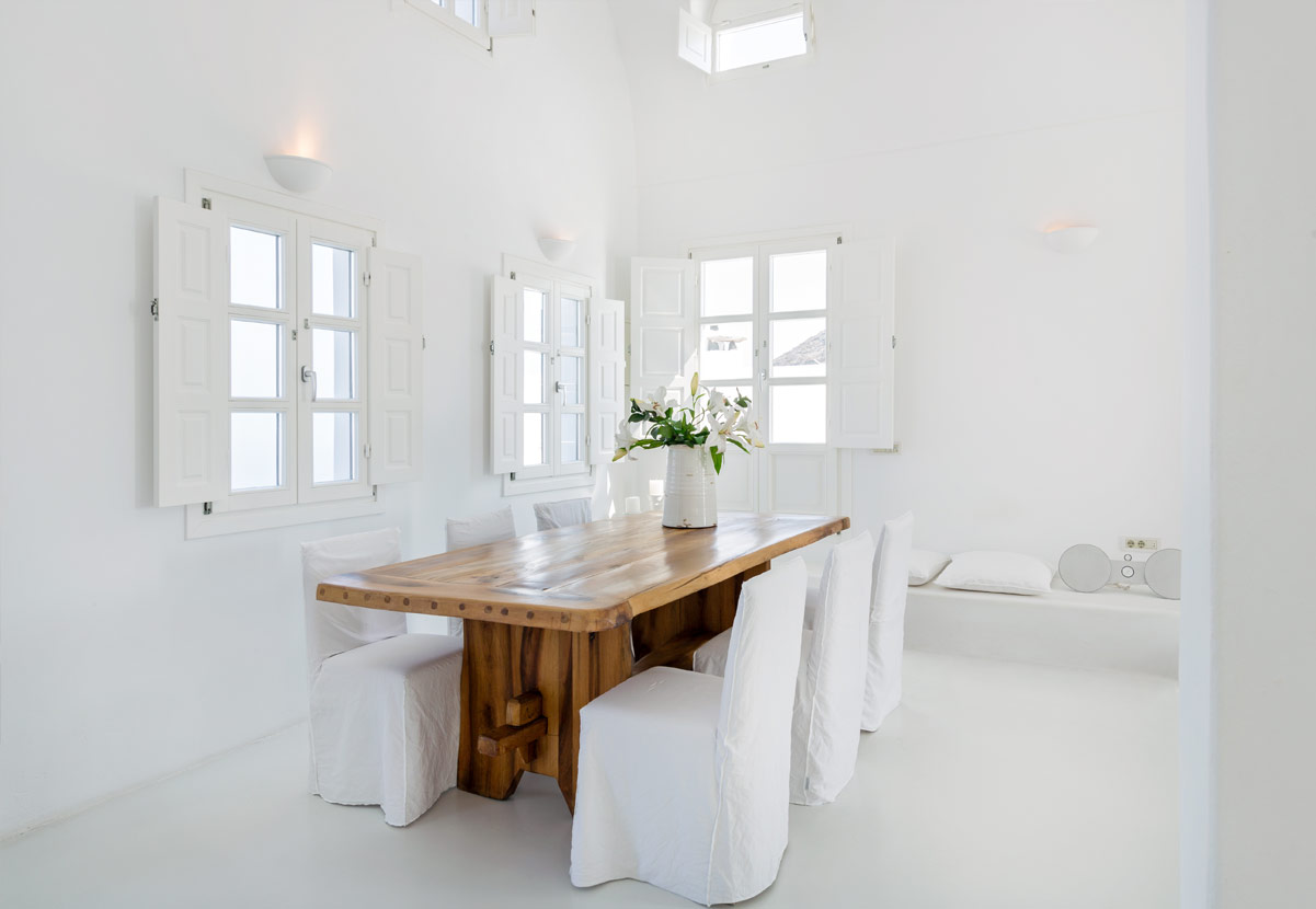All white greek island dining room with rustic wooden table.