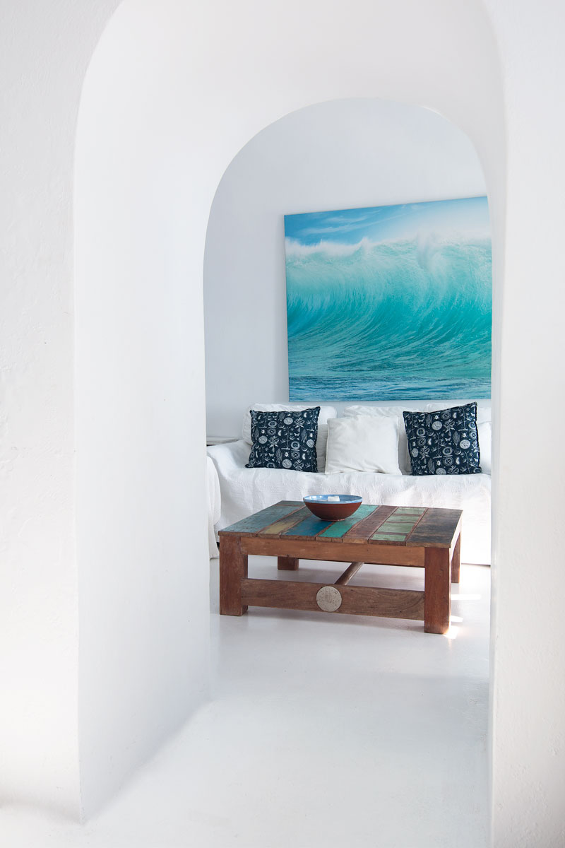 All white greek island living room with sea artwork above the sofa.