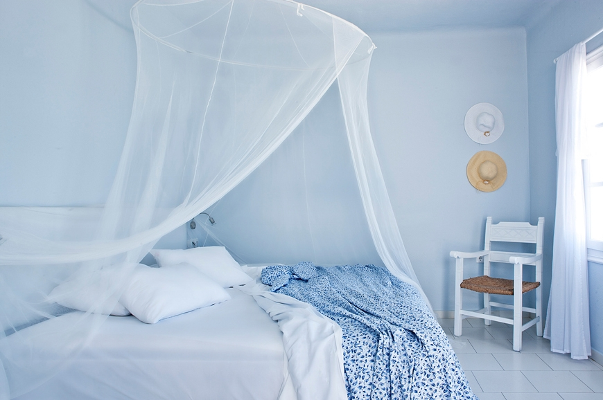 Romantic and airy greek islands style bedroom with mosquito net.