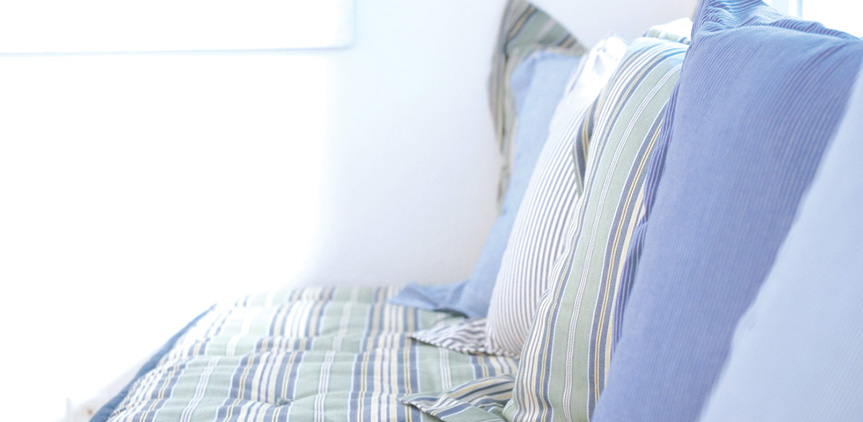 Striped blue and white pillows in greek island style interior