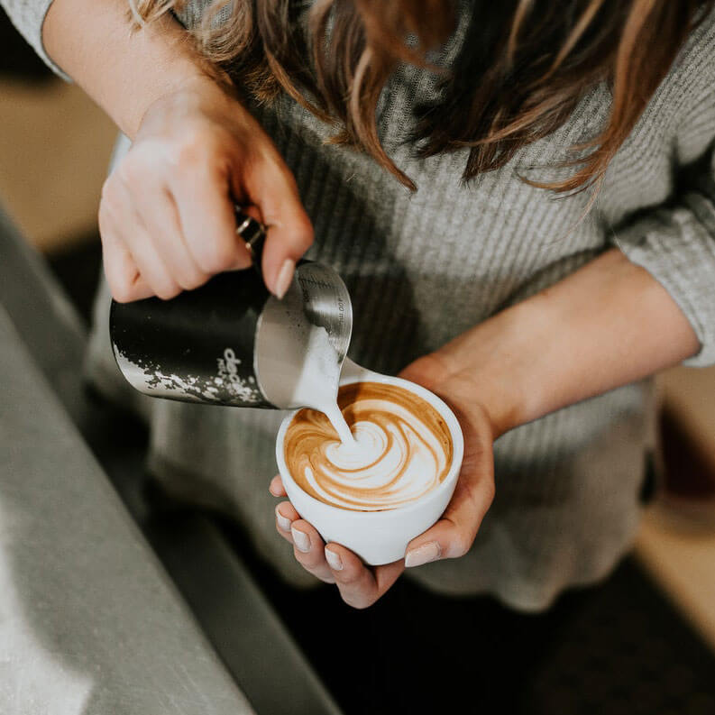 barista pouring hot milk into a coffee cup to make a flat white coffee