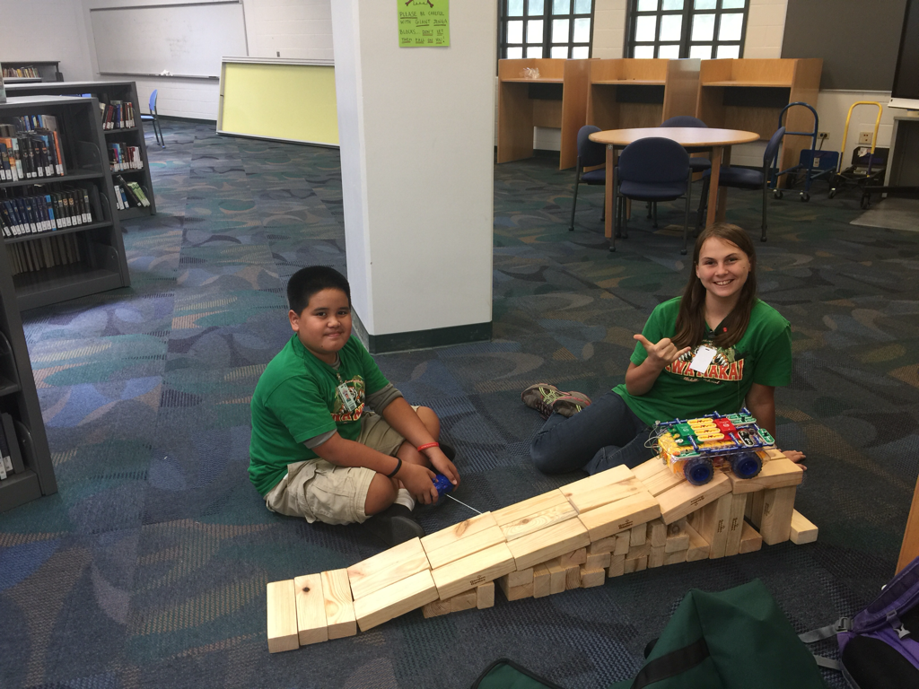 Two Ewa Makai students using wooden blocks to build a ramp for a toy car.