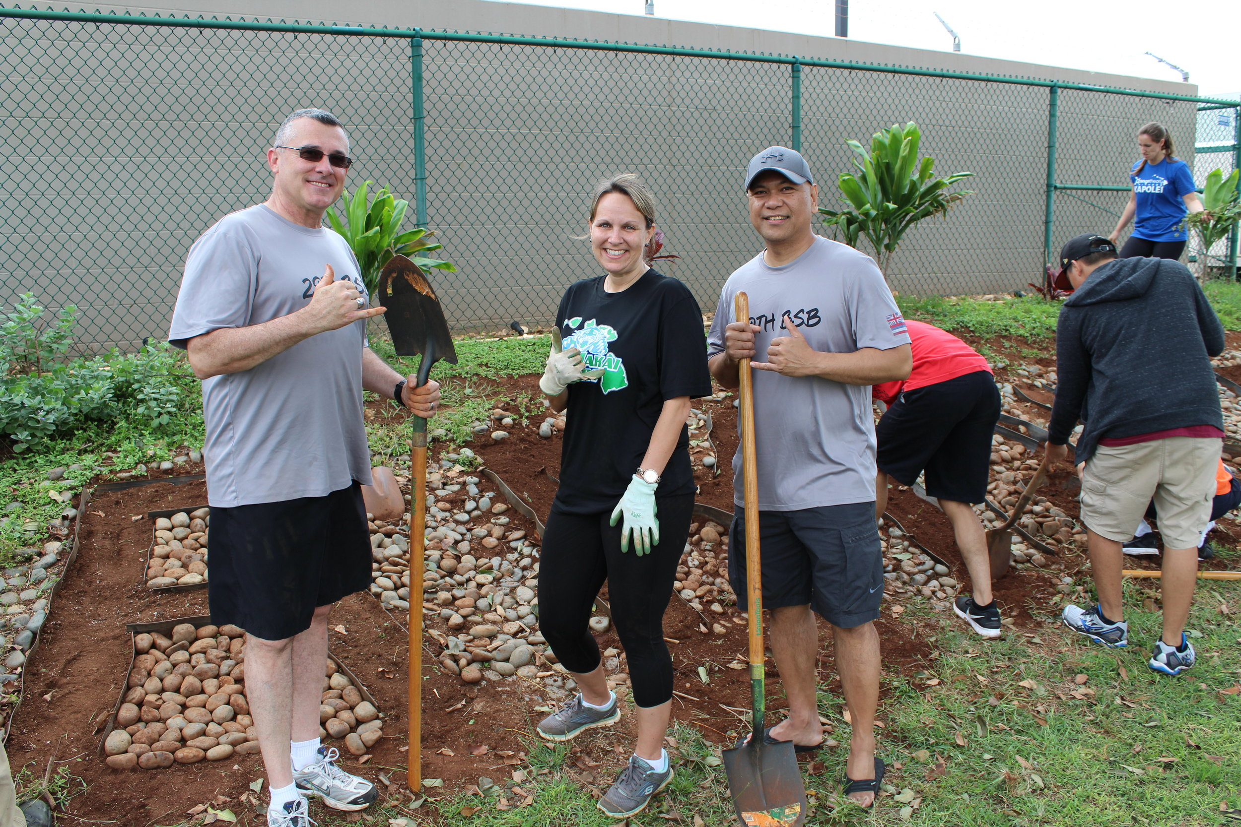 Three volunteers at Ewa Makai taking a break from the landscape project to smile for the camera.