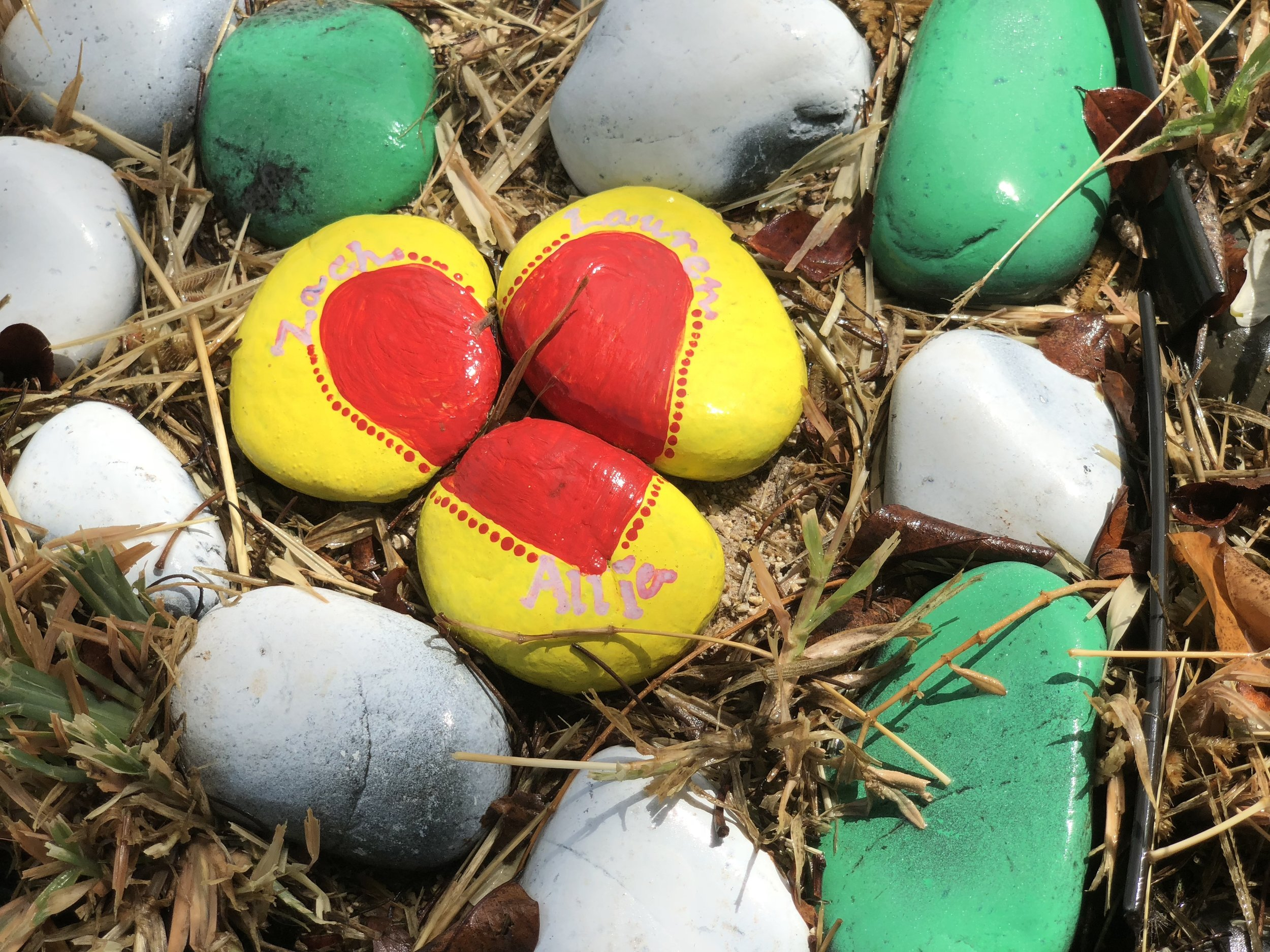 A set of three yellow and red-painted stones that are put together so that the red parts on each stone make the shape of a heart.