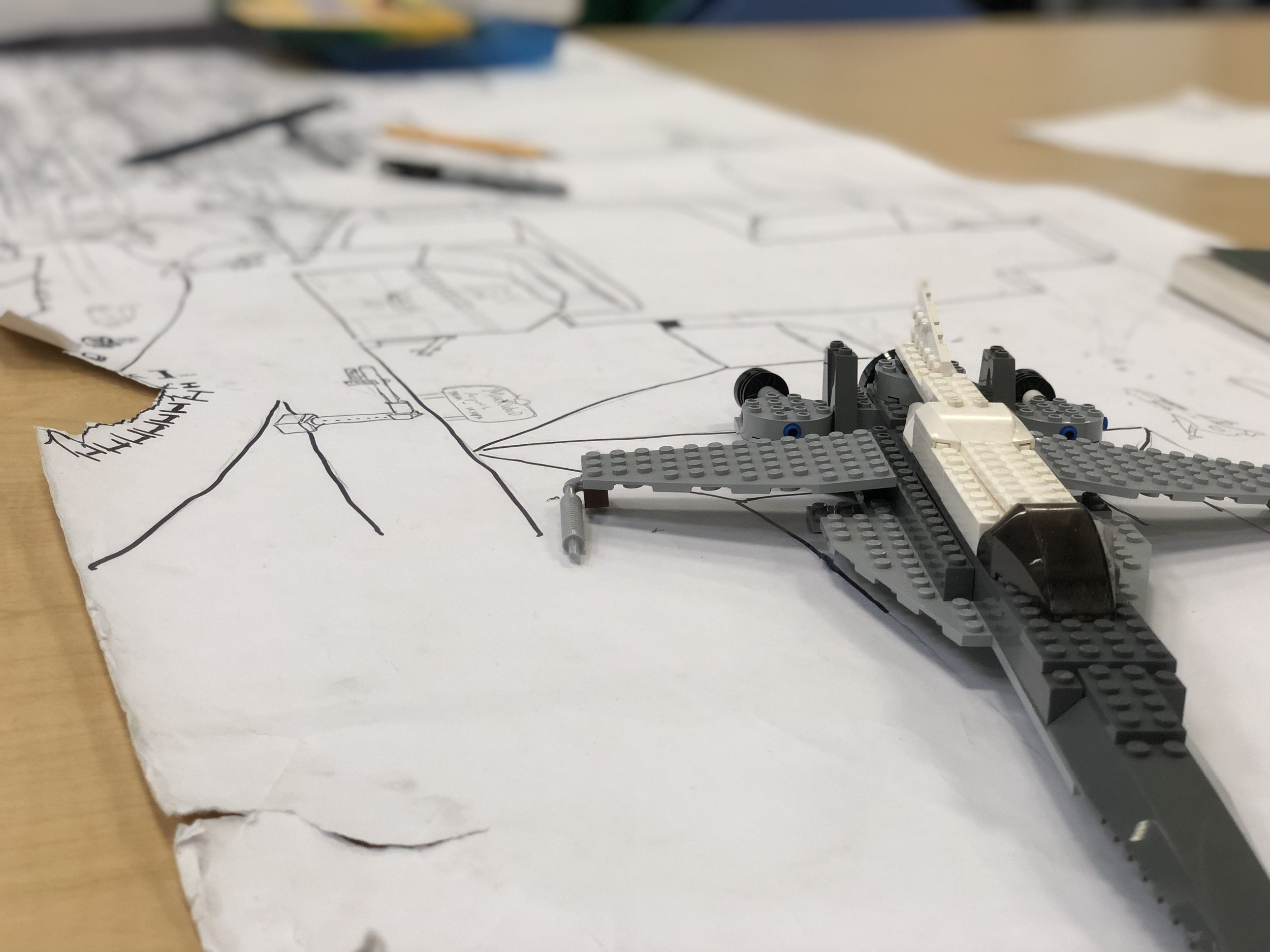 Toy aircraft made out of LEGOS on a desk.