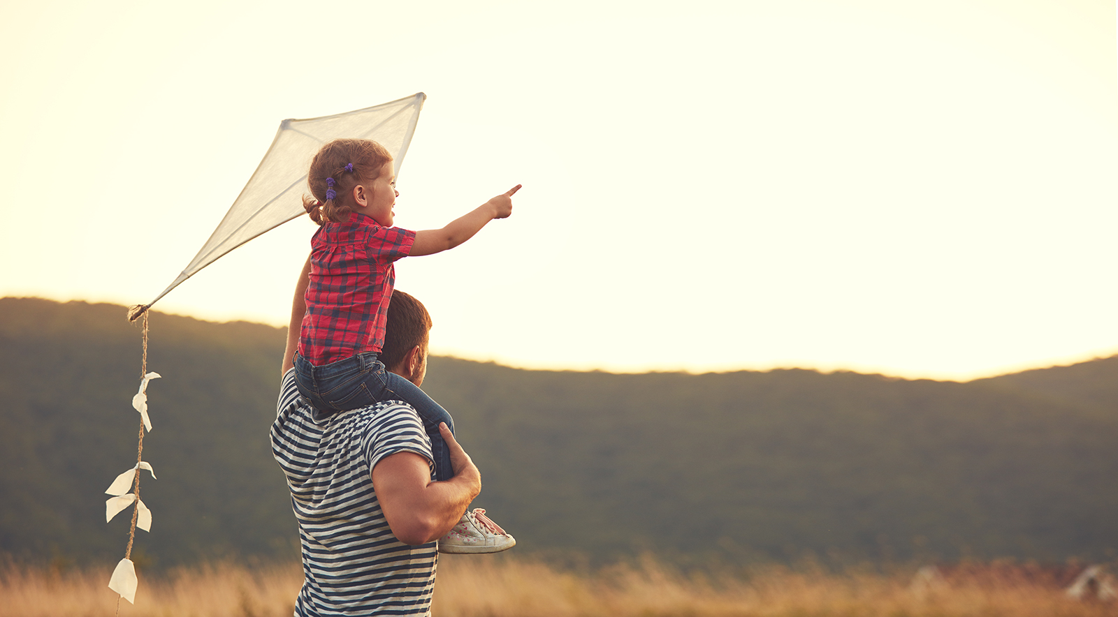child sitting on her dad's shoulders while holding a kite