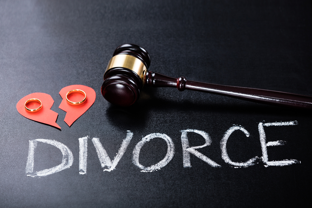 Wedding Ring And Judges Gavel With Divorce Written On The Floor