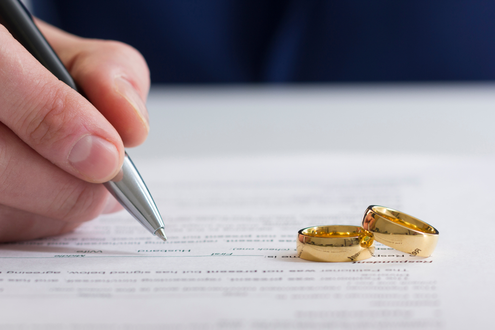 wedding rings on a divorce paper and a man holding the pen(Divorce Concept)
