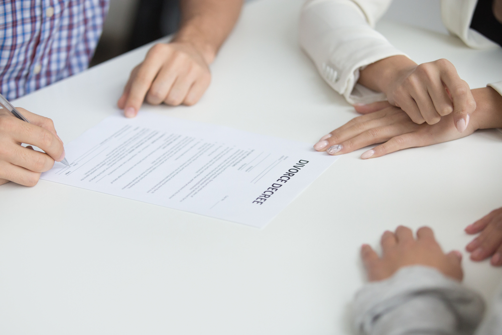 Husband signing A uncontested divorce paper