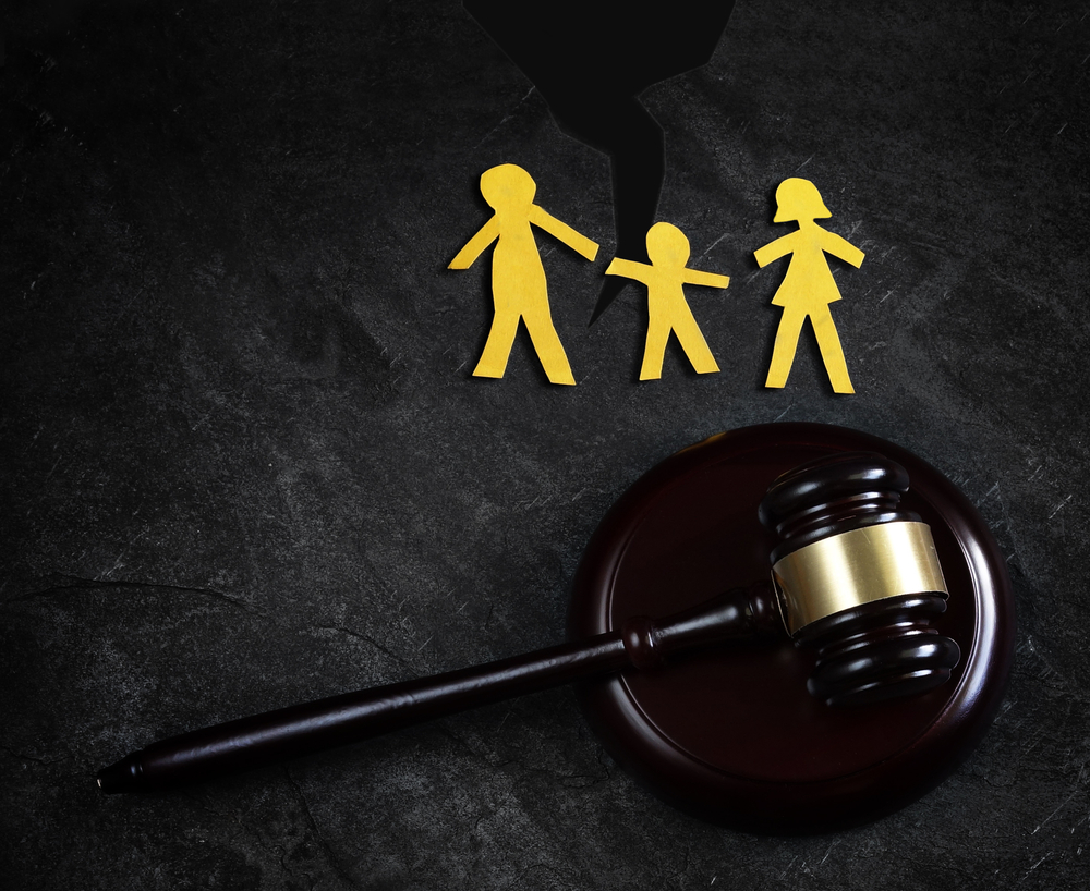 Judges gavel with a model of parents with their child