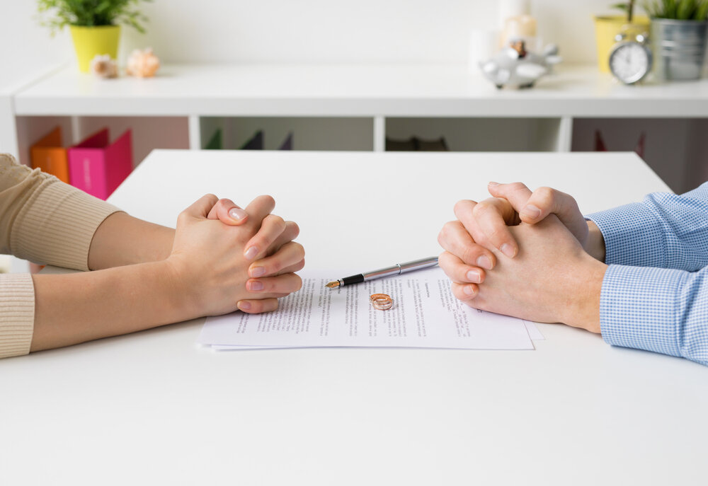 Divorce paper on desk and couple on chairs