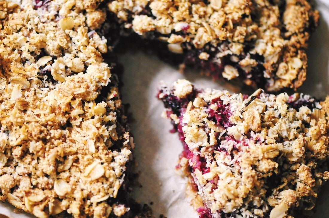 A luscious triple berry filling atop a crisp crust & topped with a delightful coconut crumble makes for one easy, healthy and delicious gluten-free and vegan dessert! #berrycrumble #vegan #glutenfree #coconut #oat #almondcrust #healthydessert #refinedsugarfree