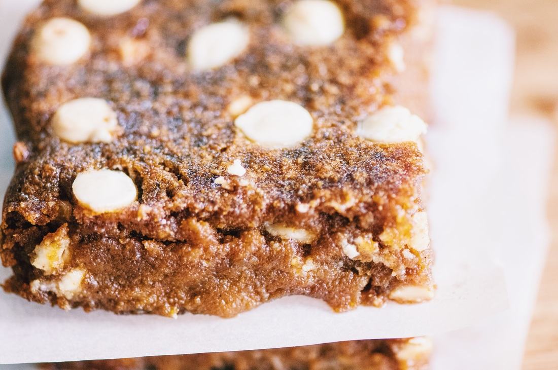 These chewy and delicious pumpkin bars make the perfect autumn treat! They are flavored by a hint of chai spices and are spotted with decadent white chocolate chips. They are not only easy to make, they also store great and are also gluten-free! You will be sold at first bite, I promise! #bars #glutenfreepumpkinbars #whitechocolatebars #chaispiced #chaibars #glutenfreedessert #autumn #glutenfree