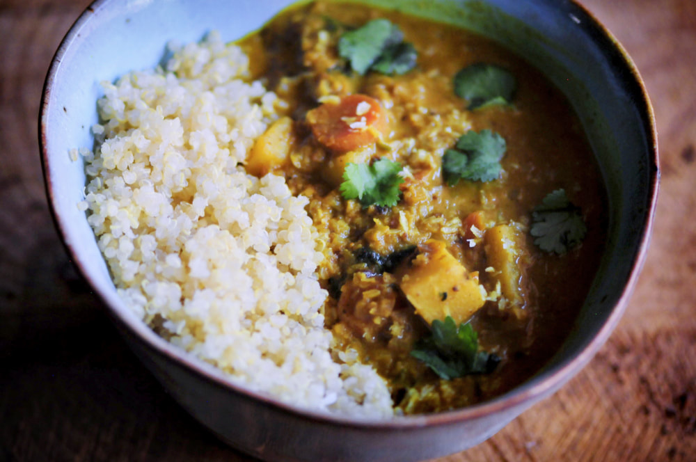 An easy, rich, healthy, and delicious curry filled with cauliflower rice, sweet potatoes, carrots, garlic, onions, coconut, ginger root, cilantro and a delectable blend of spices! Serve alongside some rice or quinoa for the perfect gluten-free vegan dinner! #vegancurry #sweetpotatocurry #caulifowercurry #indianfood #coconutcurry #cauliflowerrice