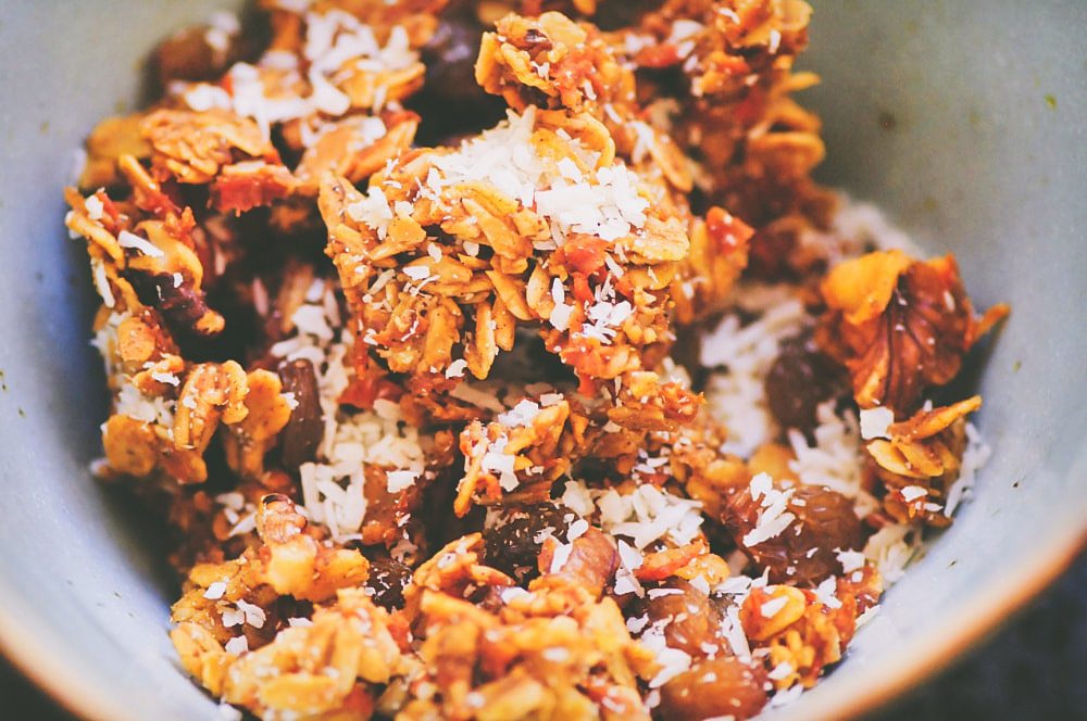 Easy, healthy, and delicious Carrot Cake Granola filled with oats, carrots, coconut, raisins, walnuts, and the perfect blend of spices! This gluten-free and vegan granola is free of refined sugars and makes a great breakfast, dessert, or snack! #carrotcakegranola #glutenfreecarrotcake #vegancarrotcake #easyhealthybreakfast #trailmix #healthysnack
