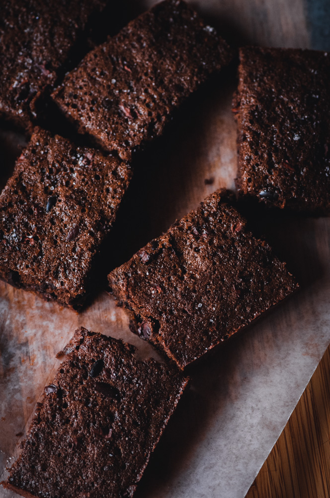 These easy and delicious Chai-Spiced Cacao Nib Brownie Bars are delightfully chocolate-y, subtly spiced, packed with iron, fiber and potassium from the cocoa nibs as well as having a diving texture. This gluten-free treat makes a great breakfast, snack or dessert as it is not over-the-top sweet (but big on flavor!). #cacaonibs #cocoa #chocolatebars #chaispiced #glutenfreebrownies #glutenfreebars #chaibars #glutenfreecakebrownies #chaispicedbrownies
