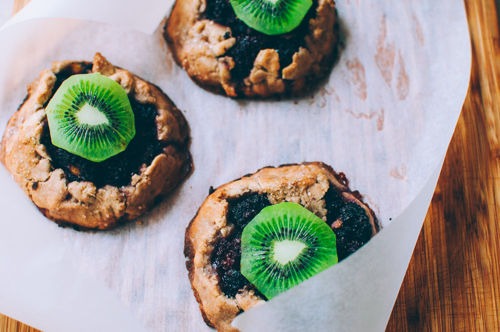 These gluten-free vegan mini rustic pies are filled with juicy blackberries and tart kiwi for a fun twist! Easy, healthy, and delicious galettes are at your fingertips! #galette #galettes #minipies #rusticepies #kiwi #blackberries #glutenfreepie #veganpie #kiwipie