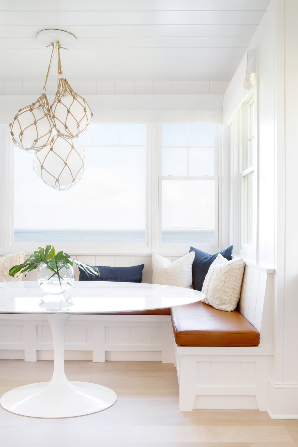 The Saarinen oval table is a perfect fit for this beautiful beachy built in seating nook by  Chango and Co . The nautical pendant and combination of earth tone and blue fabrics pick up on the natural environment beyond. the beadboard detail on the base is picked up throughout the space. well done.