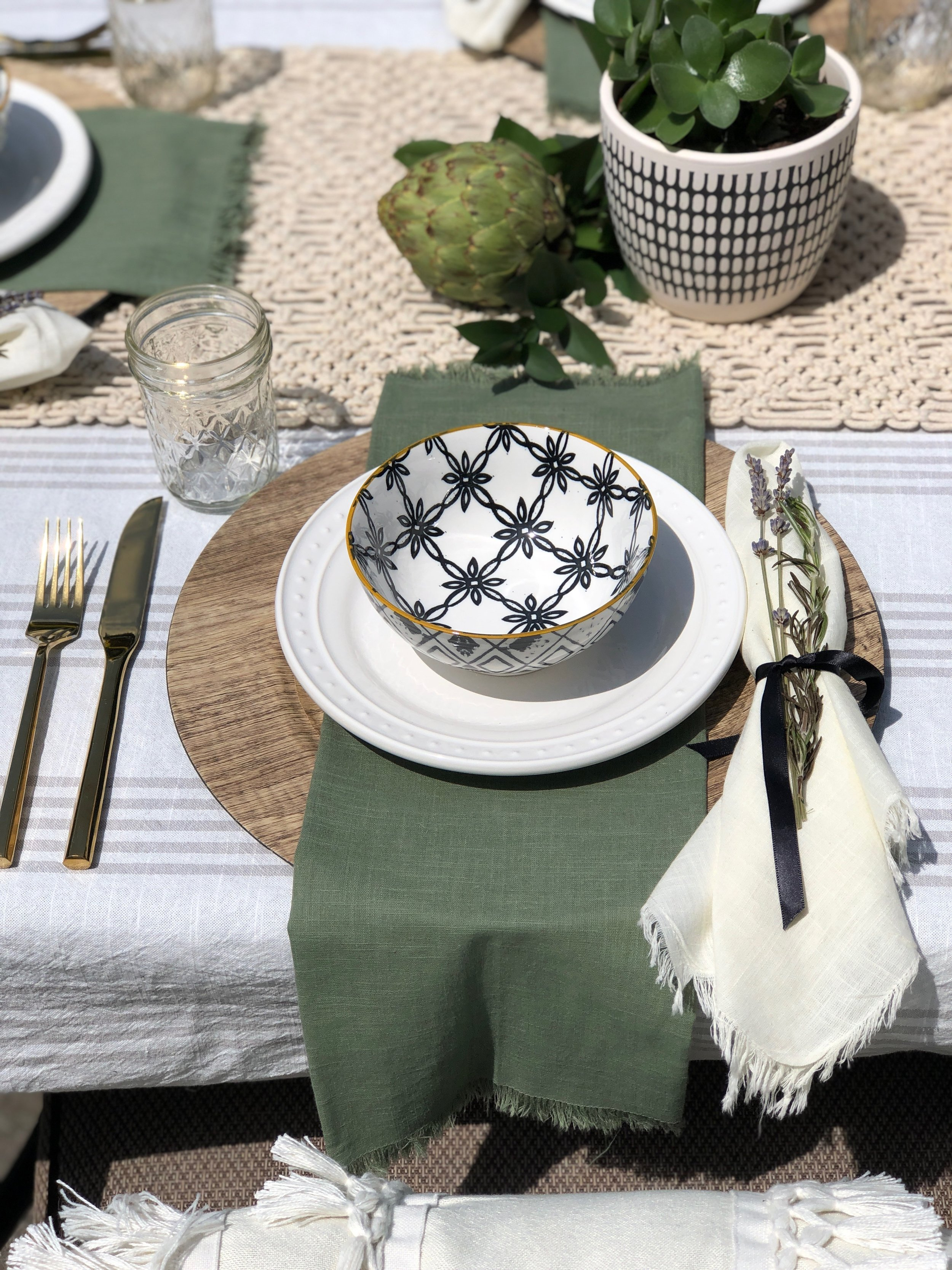 Mediterranean white, black, green and wood Tablescape by beam&bloom, World Market  White Plates ,  serving bowl ,  cloth napkins  and  macrame table runner . Target  flatware  and  tablecloth .  At Home  chargers and bowls. Photo Credit: Campbell Minister with Decorated Interiors