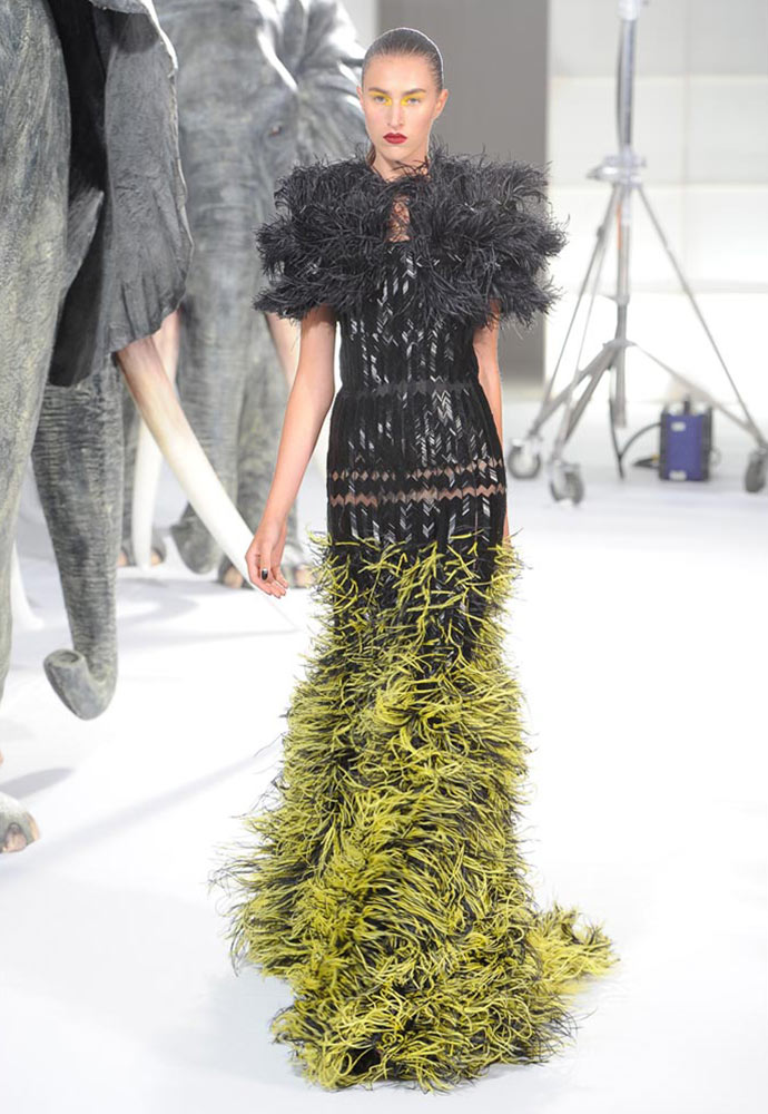 HERRINGBONE FEATHERED FISHTAIL GOWN WORN WITH LEATHER BEADED AND FEATHERED SHOULDER CAPE