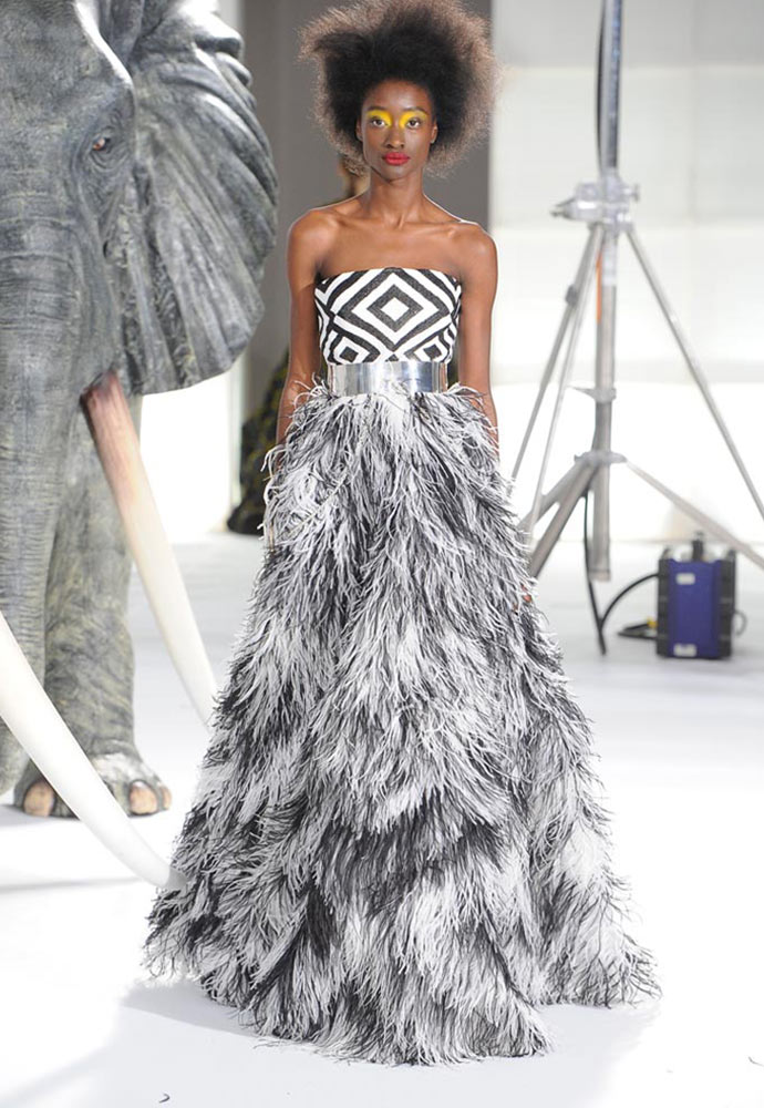 ZULU GRAPHIC SEED BODICE WITH OSTRICH FEATHER SKIRT WORN WITH SILVER BELT AND HAND CUFFS