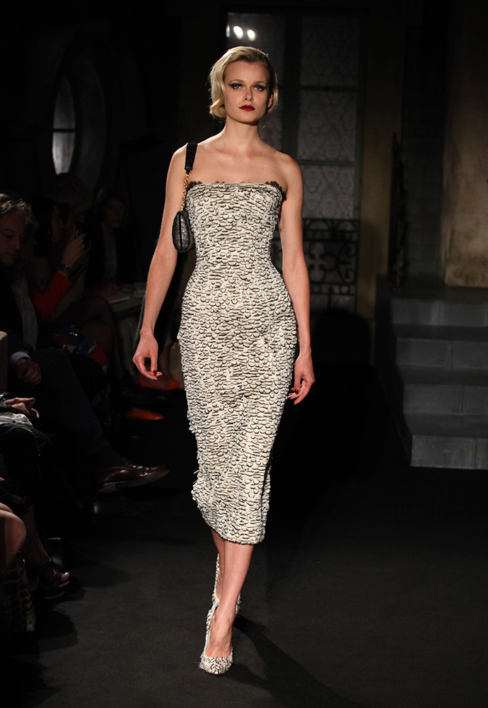 White feather strapless corset dress, long black crocodile clutch bag with fox tail and white feathered shoes