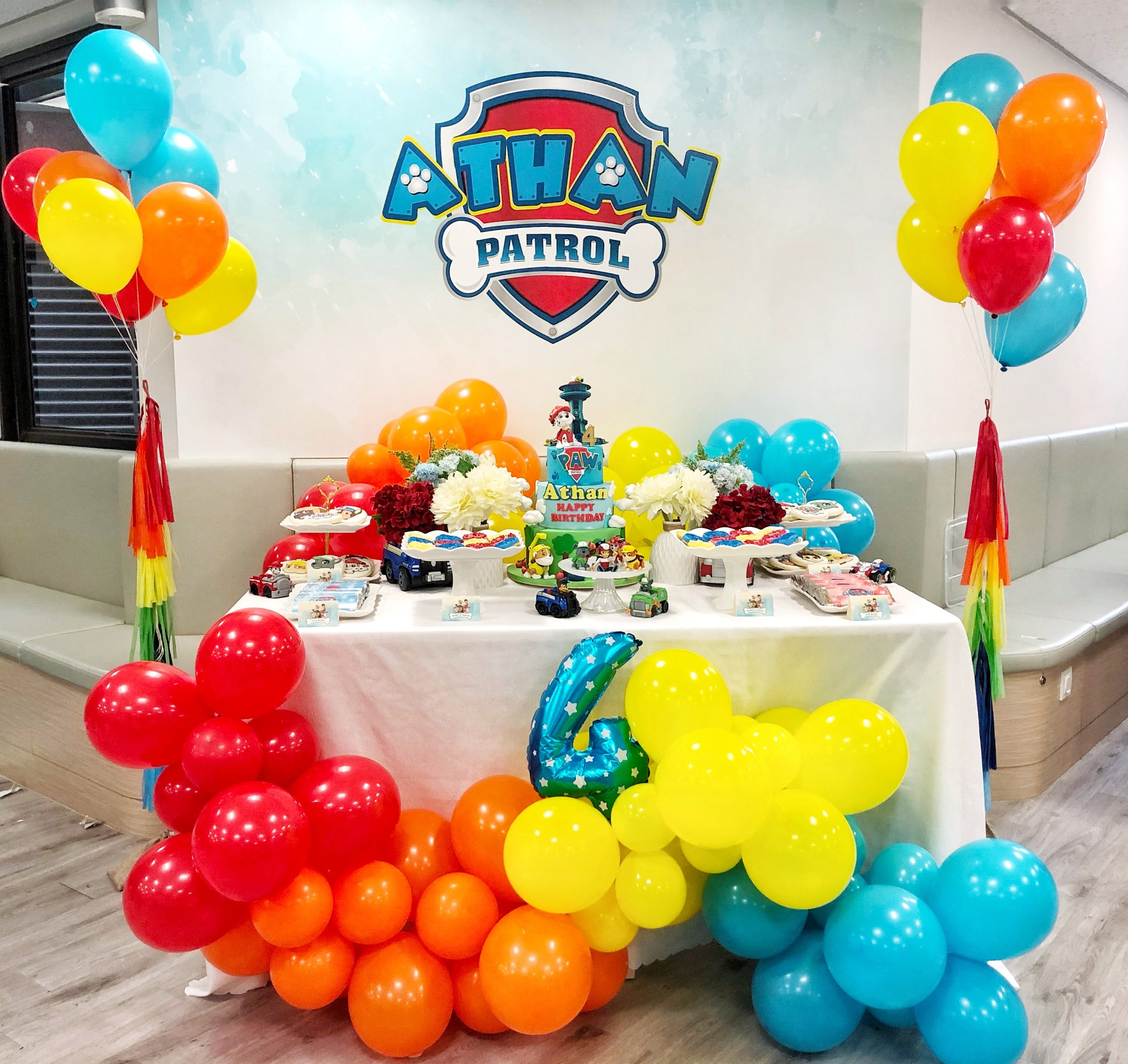 Rolling Out The Pups - Athan's Paw Patrol party had all these fun, bright colors that we wanted to anchor it down on something simple and subtle. We intentionally designed the backdrop to be lighter and to have only one focal point, the custom badge, to perfectly complement our table. The dessert table had key Paw Patrol accents such as vehicles (used as vases for our florals) and characters amidst white servingware to tone everything down. We used rainbow balloon garlands and bouquets to make this table extra special. Desserts were rainbow mini donuts, custom wrapped chocolate bars, and character cookies - all of which looked so gorgeous on the table!