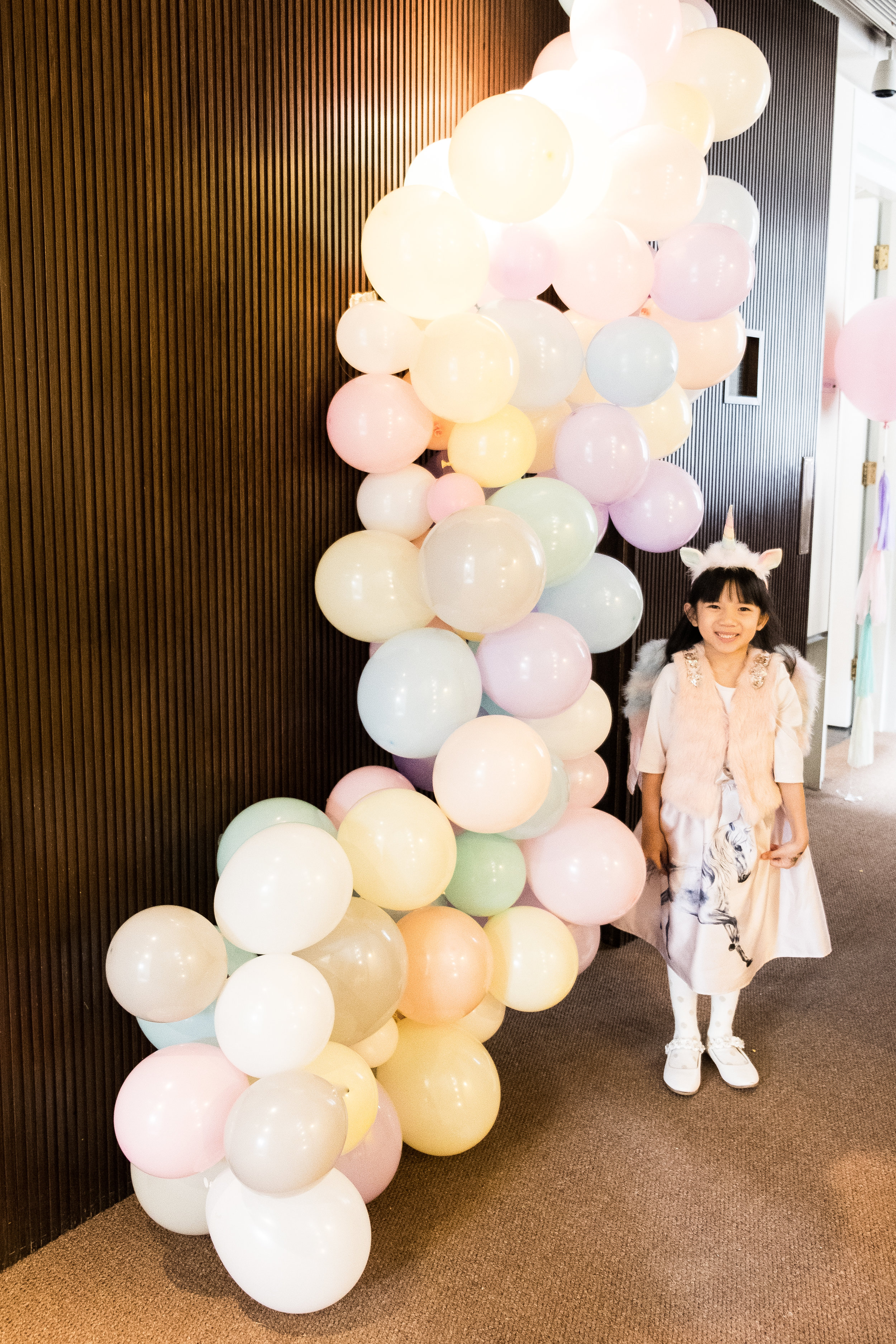 Be A Unicorn in a Field of Horses - We decorated the entrance with this beautiful macaron balloon garland which led guests to the function rooms marked with three large helium balloons with pretty pastel tassels and the windows lined with pretty favor bags. Chloe had so much fun helping us blow up our balloons!