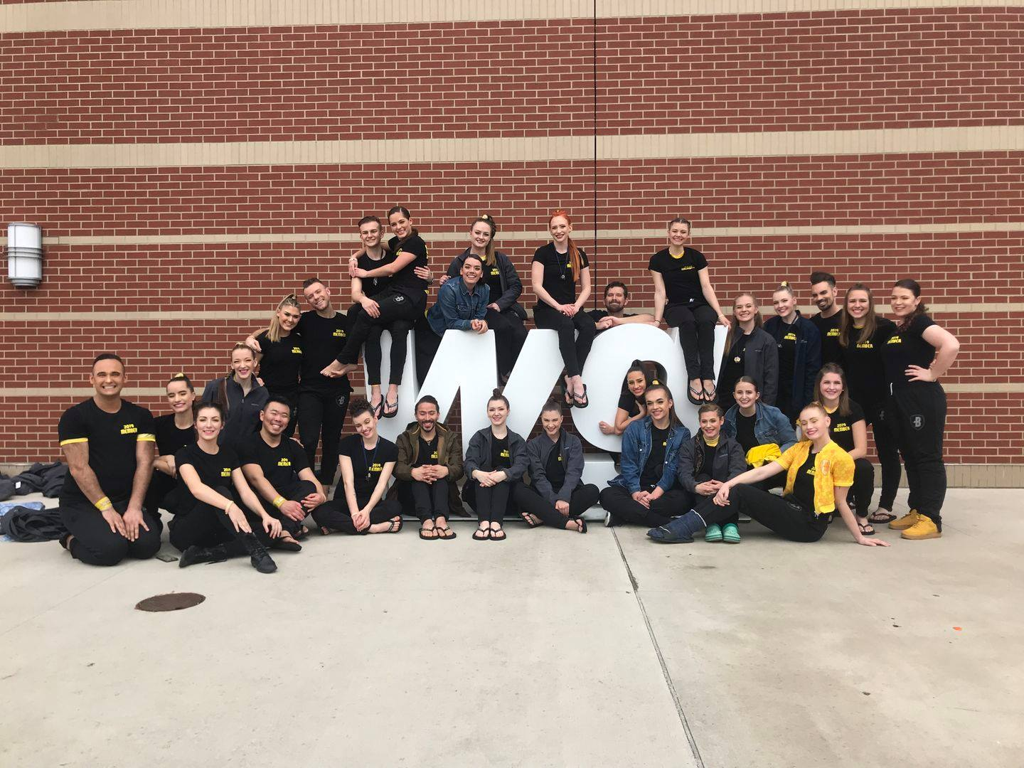 Before going to semis warm-up, performers took a group picture by the WGI sign!