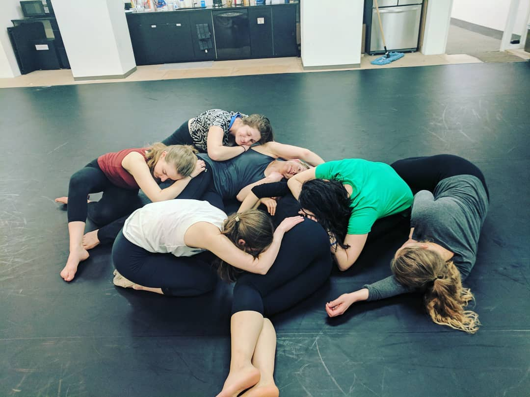 Dancers laying on top of each other about to end a dance.