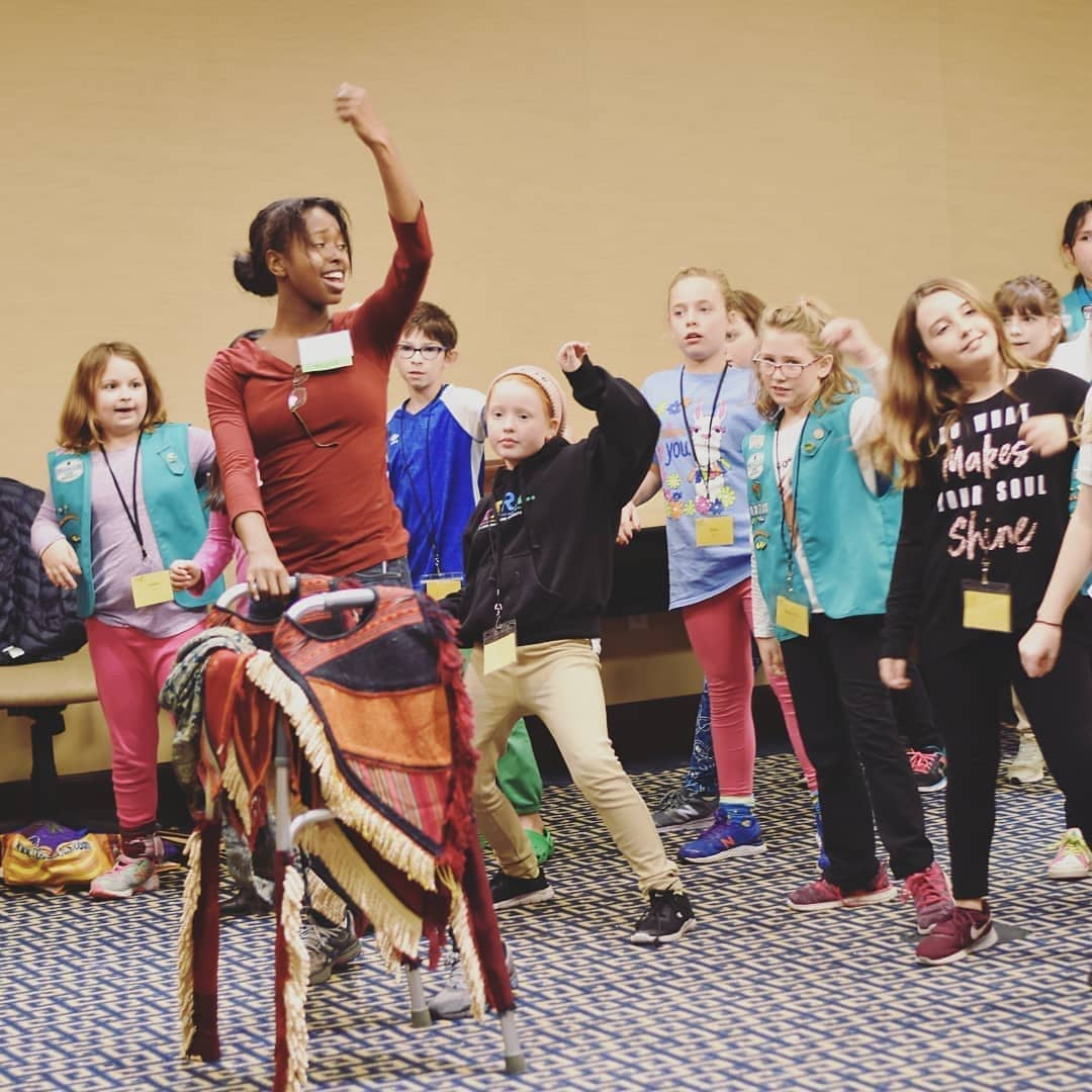 Director Ellice holding one arm up with the other on the wakanda walker with a group of Girl Scouts following behind her.