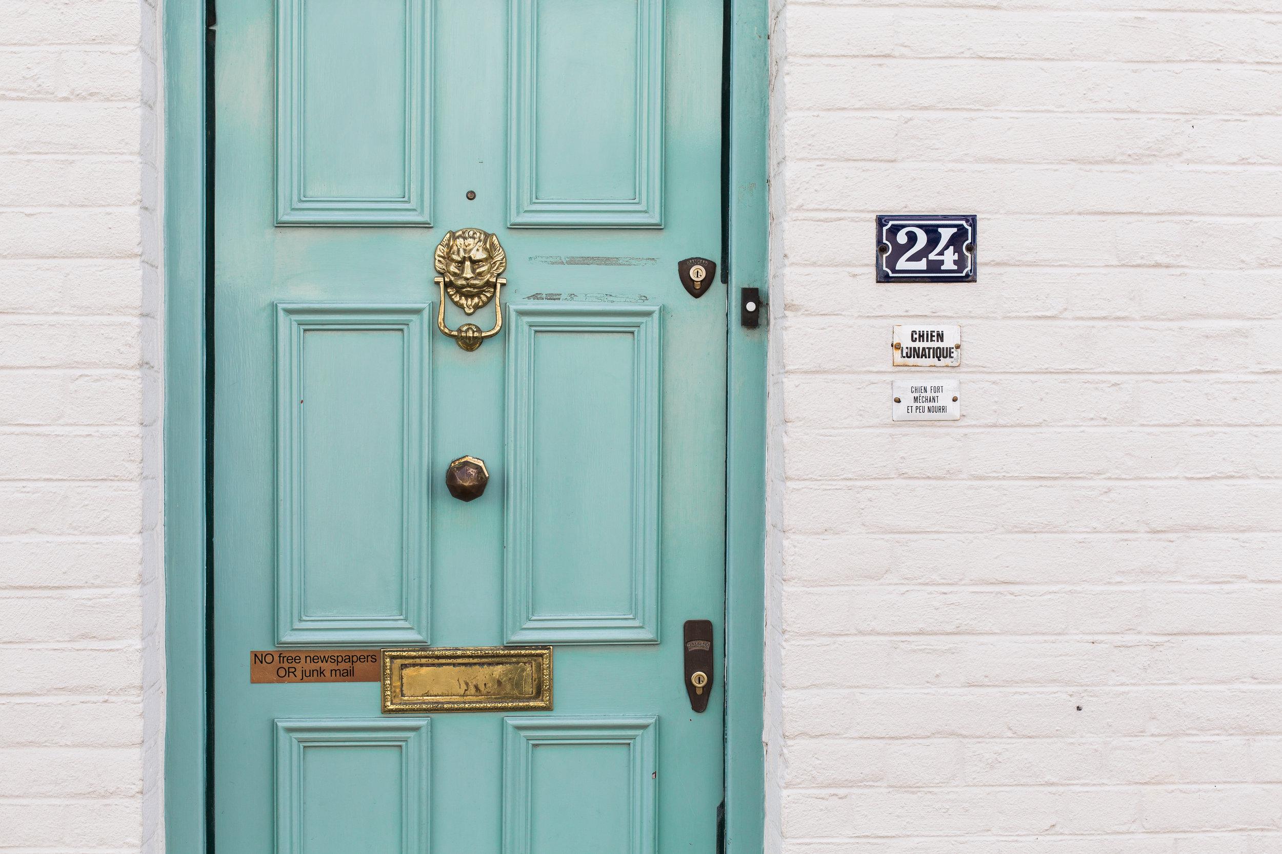 turquoise front door white brick house