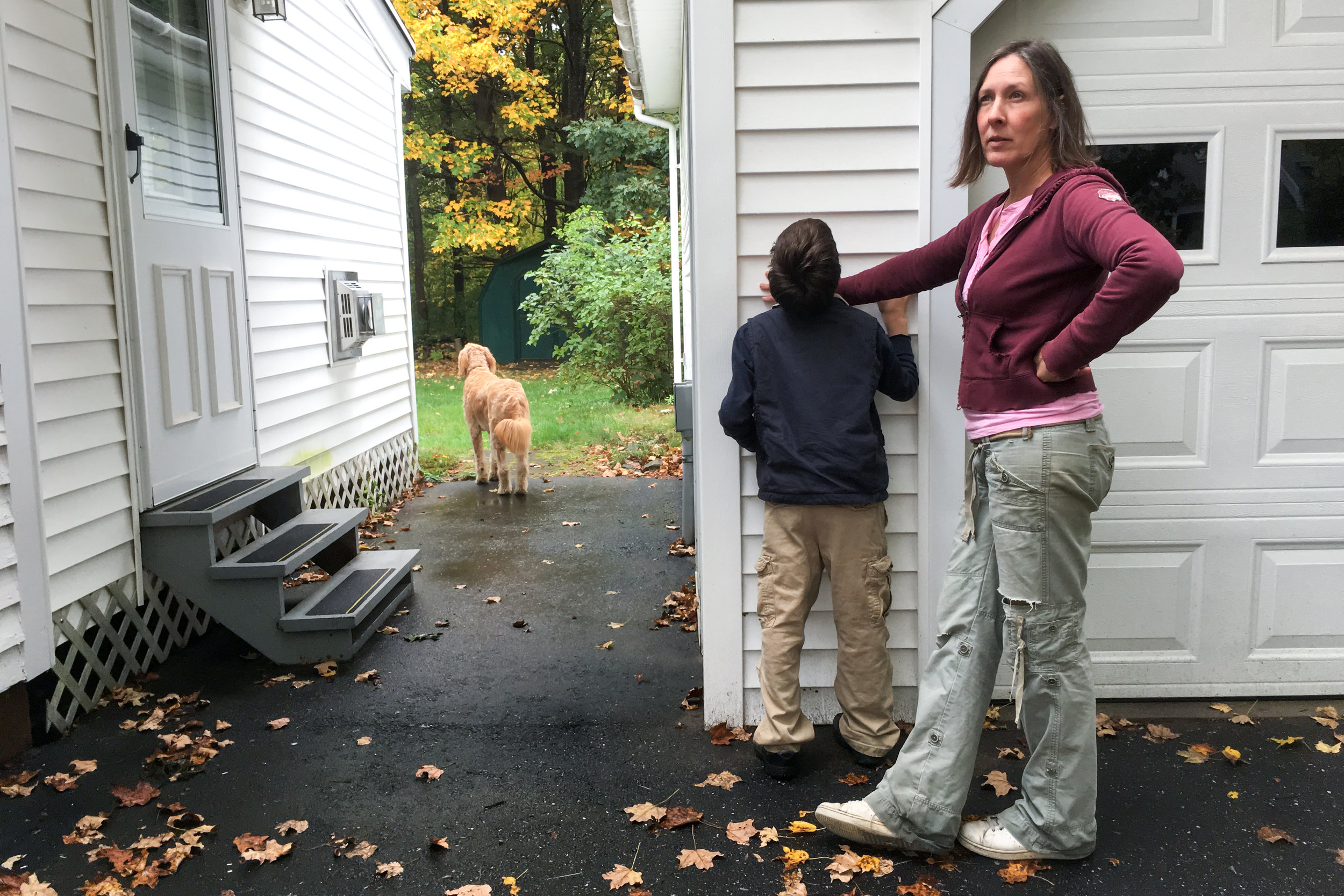 """He has his favorite spots."" Christy Shake blocks her son from biting at the siding on a neighbor's house while their dog, Nelly, looks for squirrels in the yard on October 8, 2017 in Brunswick, Maine.  Calvin is very tactile and likes the feeling of his teeth against hard surfaces, and, because of his very poor vision, he is drawn to clear patterns of contrasting light and dark."