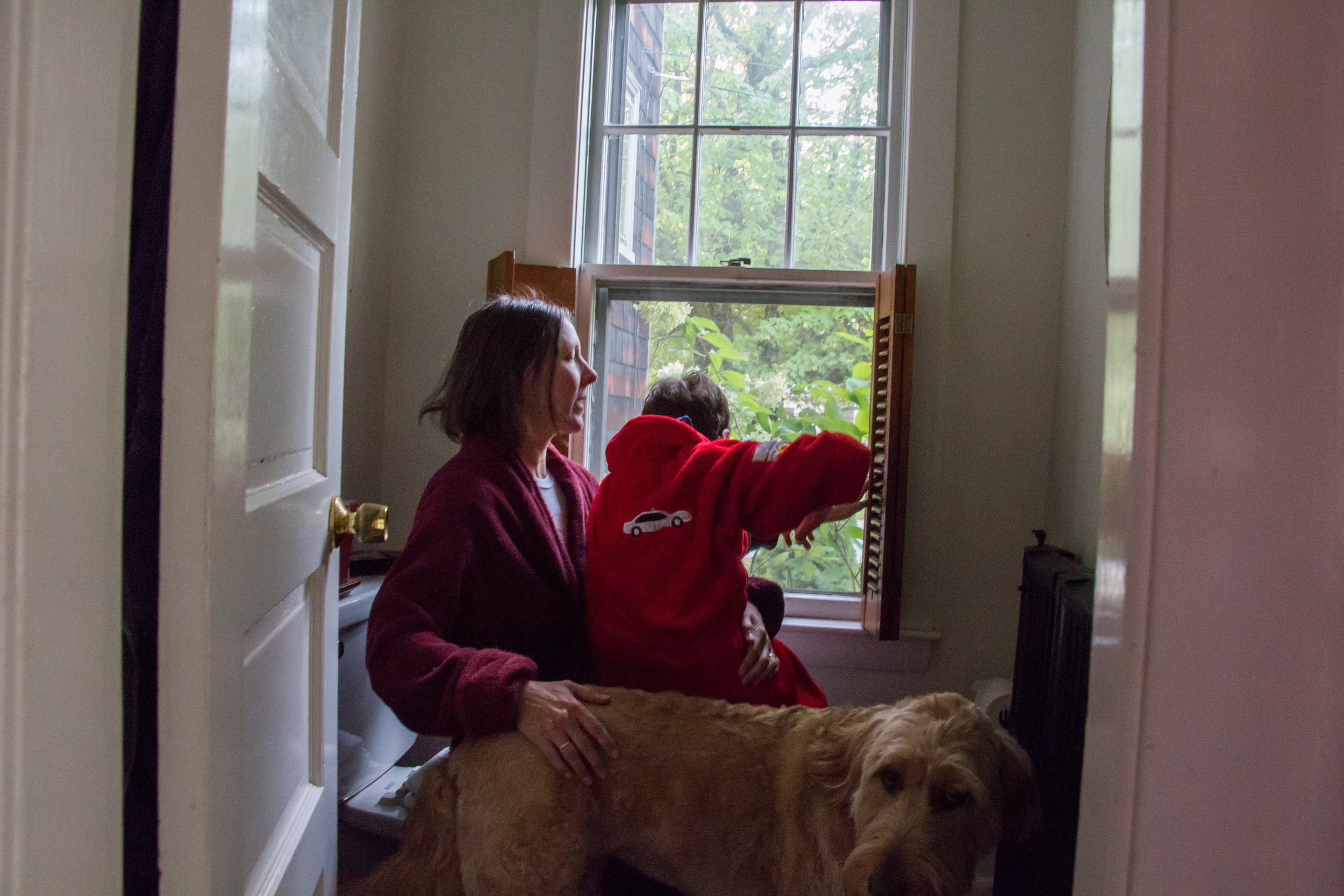 Christy Shake braces her son Calvin as he looks out the window of their home in Brunswick, Maine on September 30, 2017. Though Calvin can walk on his own now, his balance and vision are not good, and he can easily fall without Christy nearby to catch him. Much of their routine when he is home consists of her following him from room to room.