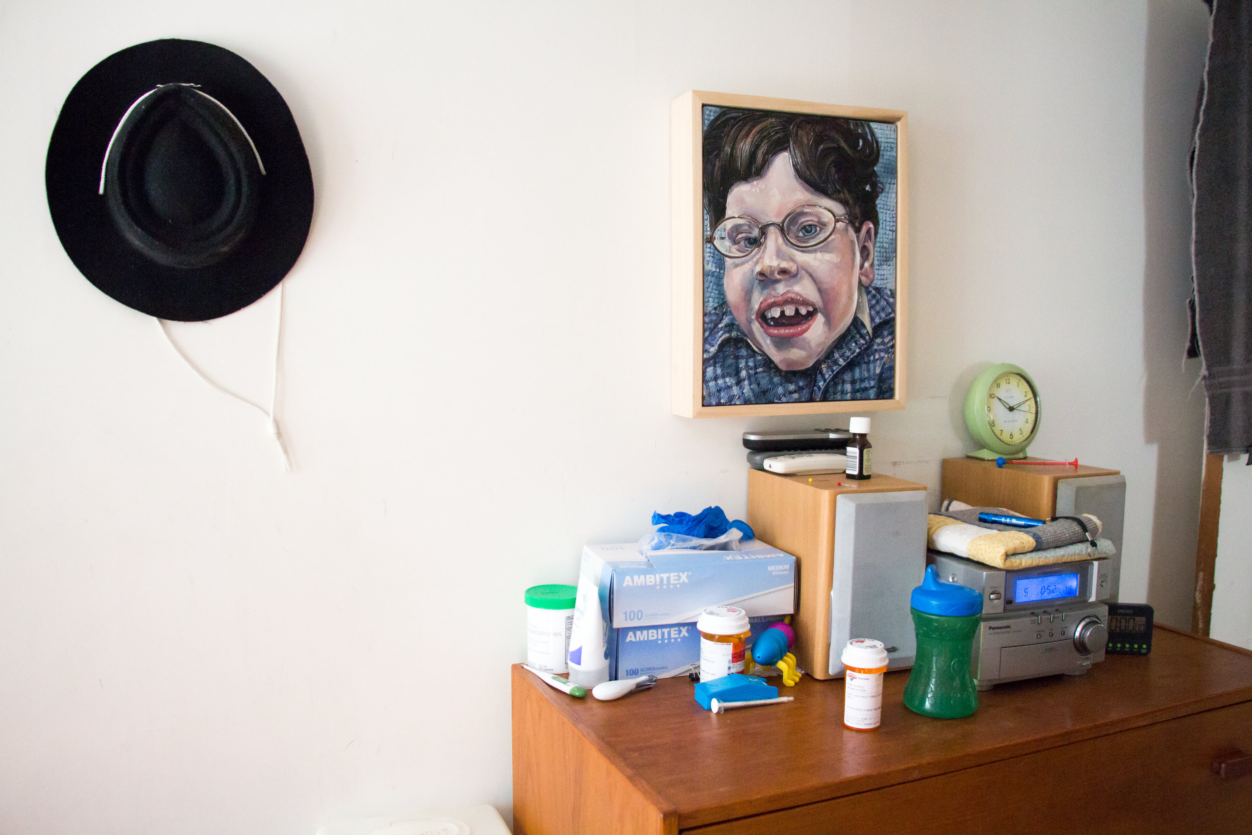A portrait of Calvin hangs above a dresser covered with medications and medical supplies in his bedroom on September 30, 2017 in Brunswick, Maine. Calvin doesn't sleep very well and wakes up several times a night. Christy gets up to soothe him, cover him with his blanket, or give him a dose of medication.